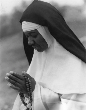 Photo of a Dominican Nun with praying hands displaying her Rosary