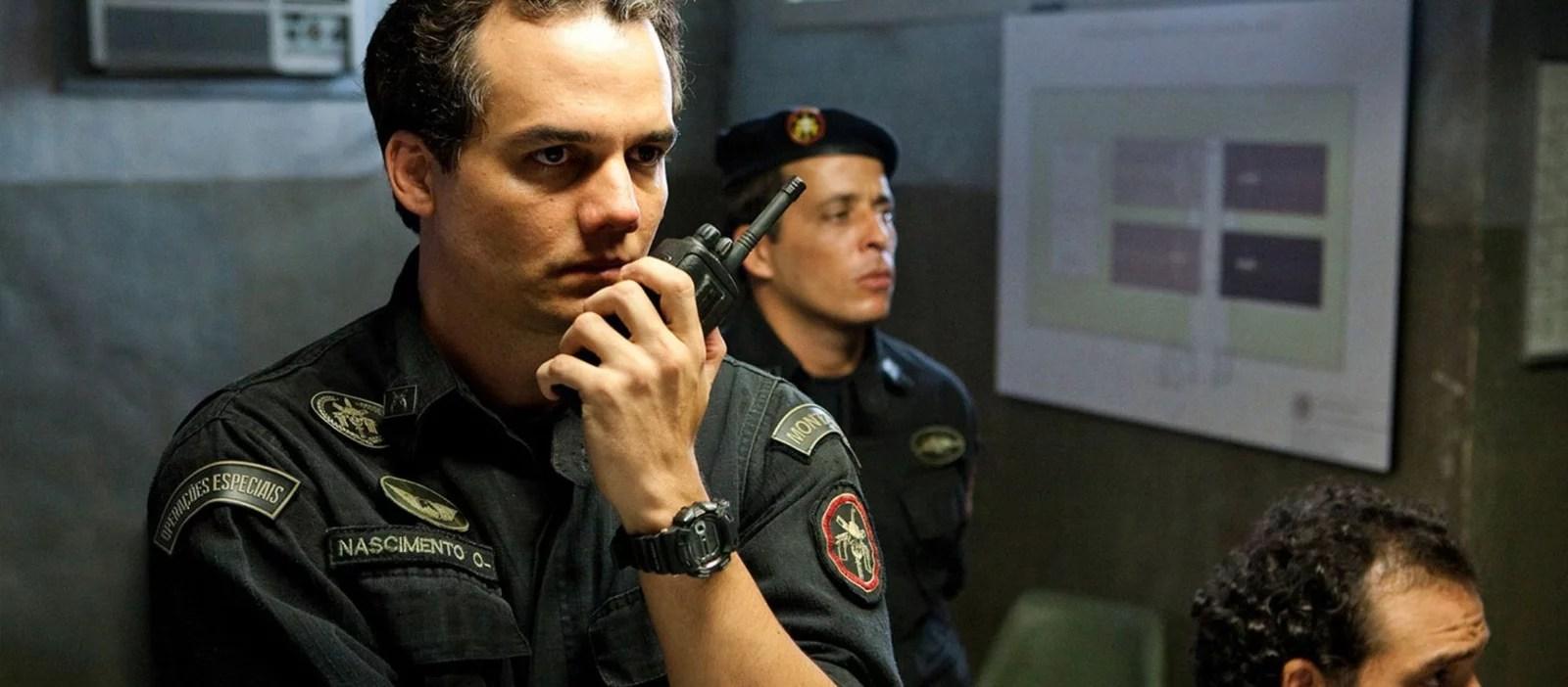 Capitão Nascimento em cena do filme Tropa de Elite pensando com a mão no queixo