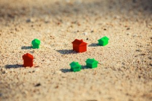 Small red and green plastic houses in the sand on the beach