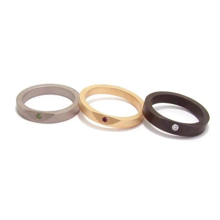 'Less Is More' ringen, titanium met groene diamant, gematteerd geelgoud met paarse diamant en zirkonium met witte diamant