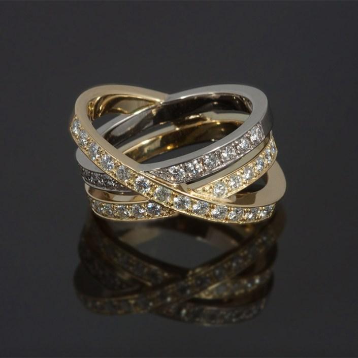 Ring gemaakt van geel- en witgoud en rondom pavé bezet met briljantgeslepen diamanten.