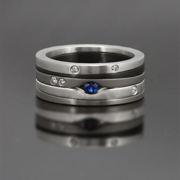 Ring gemaakt van zirkonium, witgoud, edelstaal en titanium, bezet met een blauwe saffier en witte diamanten.
