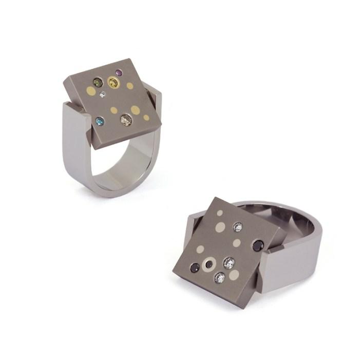 Ring 'Two Faces', een ontwerp met twee gezichten. In dit geval is de titanium plaat aan de ene zijde bekleed met platina stippen en witte en zwarte diamanten en aan de andere kant met geelgouden stippen en divers gekleurde diamanten.
