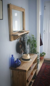 Rustic hallway furniture, custom made to your specifications. Country entrance hall, with solid wooden hall table and three wood bookshelves, also for shoe storage. Blue glass ornaments, green house plants and red persian runner leading to front door. Large wall mirror with shelf and 5 black iron hooks, holding scarves and handbags.
