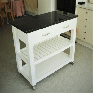 this kitchen island trolley has a high quality solid granite worktop and 2 shelves. The upper shelf is in slatted wood to aid the circulation of fresh air and increase the shelf life of your fruit & vegetables. Designed and custom handmade to any size by Marc Wood Joinery in Somerset UK.