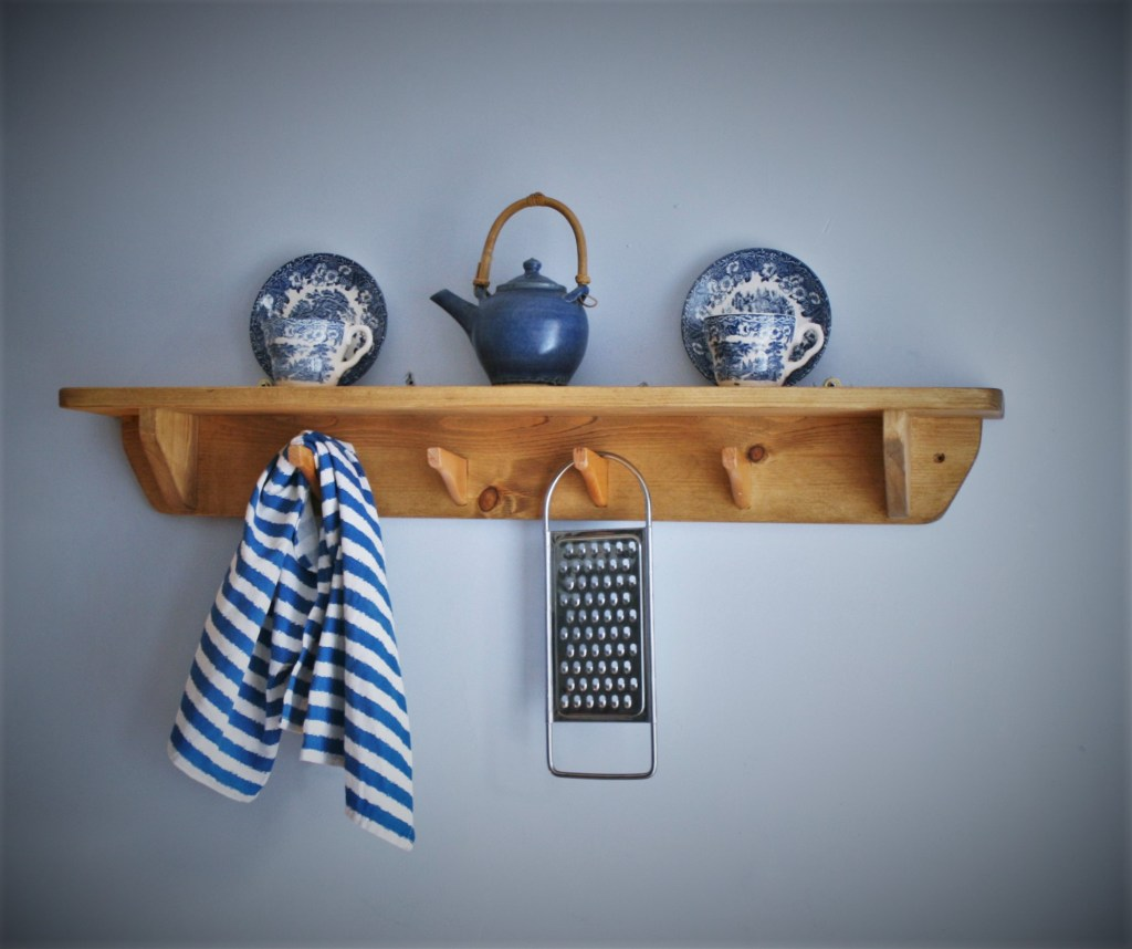 Our modern rustic custom handmade wooden kitchen wall shelf measures 90 cm height long and has been inspired by the clever re-use and upcycling of wooden coat hanger hooks to be used as tea towel hooks, for cookery aprons or to store light kitchen equipment. Our design is based on traditional west country farmhouse country kitchens and each piece of kitchen furniture is handmade by Marc Wood Joinery in Somerset UK from eco sustainable and reclaimed wood. Our wide kitchen wall shelf with upcycled hooks can be custom made to any size and we can arrange delivery or installation near Somerset, Dorset, Devon, Bristol or Exeter.
