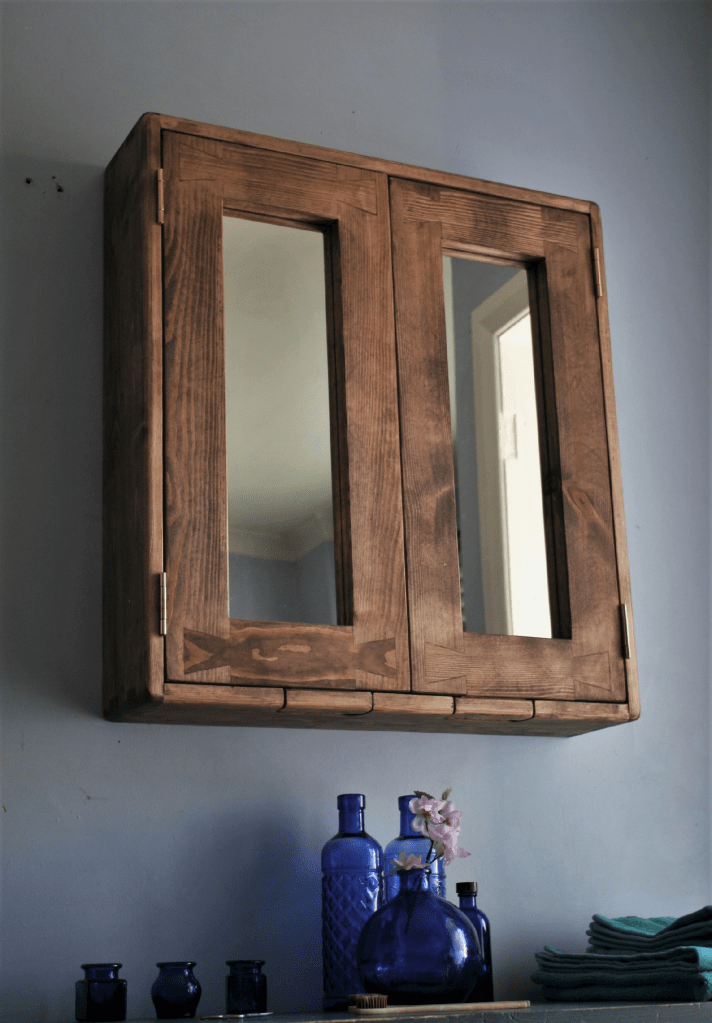 Bathroom cabinet with double mirrored doors in natural wood stained with a dark toned Danish Oil