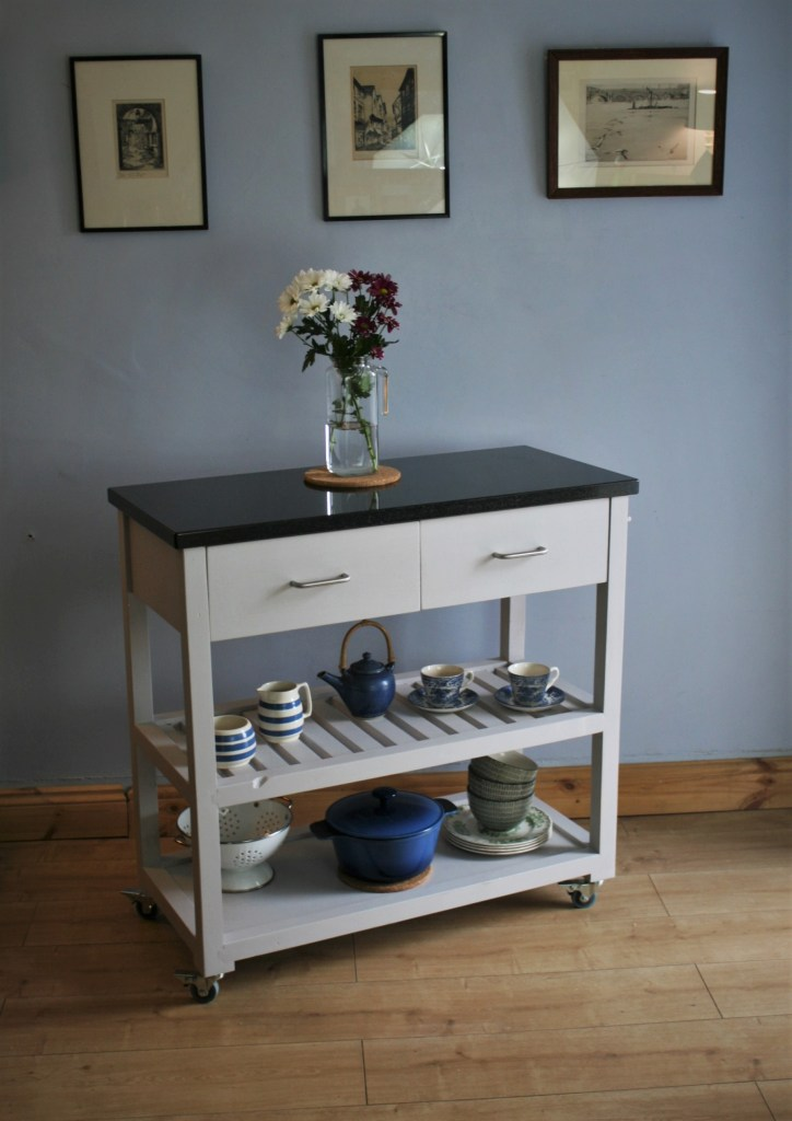 Our portable classic kitchen island trolley in a pale grey finish is handmade from sustainable natural wood with a solid black granite worktop and chrome towel rail; contact Marc Wood Joinery in Somerset for custom made kitchen storage.