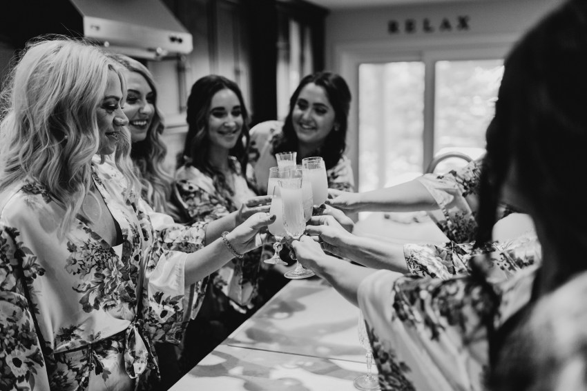 bridesmaids cheers for bride on morning of wedding day in toronto, ontario