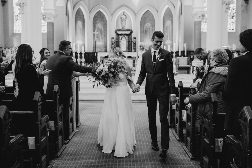 bride and groom walk down aisle at st peters basilica in london, ontario