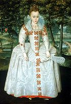 A full length portrait of a young girl wearing a large pale dress, with tight jewelled bodice, and long sleeves.  She has brown hair, and wears a tiara.  In her left hand she holds a fan.  Behind her, a small river runs underneath a bridge, in a small glade filled with trees.