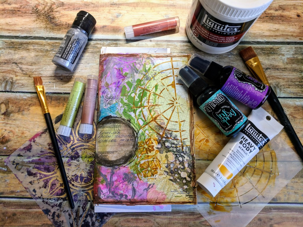 A painted art journal page with bottles of ink and paint scattered on the desk around it