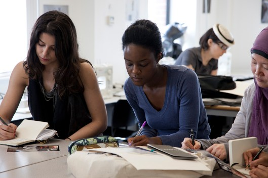 Photo: fashion design students work in classroom on ideas for fashion competition, photography by London Photographer