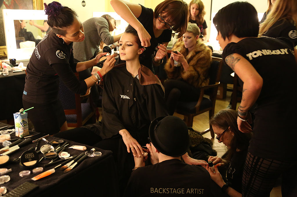 Photo: behind the scenes at Fashion Scout catwalk prep on model by creative team. Photographer London