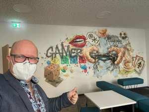 Herr Thieswald, geschäftsführender Gesellschafter aller ASPIDA-Unternehmen und das Wandgemälde