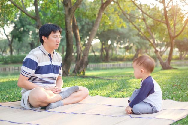 Asiático pai com os olhos fechados e criança de menino de 1 ano de idade criança pratica ioga & meditando ao ar livre na natureza no verão, conceito de estilo de vida saudável Foto Premium