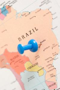 Blue plastic thumb tack pin inserted in a map of Brazil, conceptual of travel destinations and planning a summer vacation