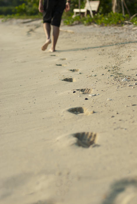 Person walking away across a beach leavng barefoot footprints in the sand during a walk on a sunny summer day on vacation