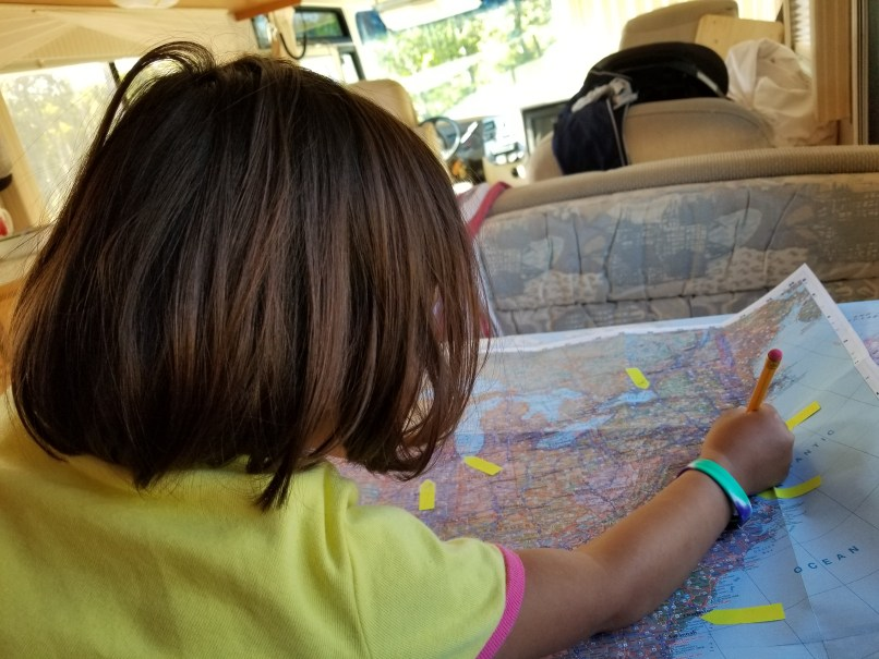 4-year-old girl pointing to New Jersey on a map.