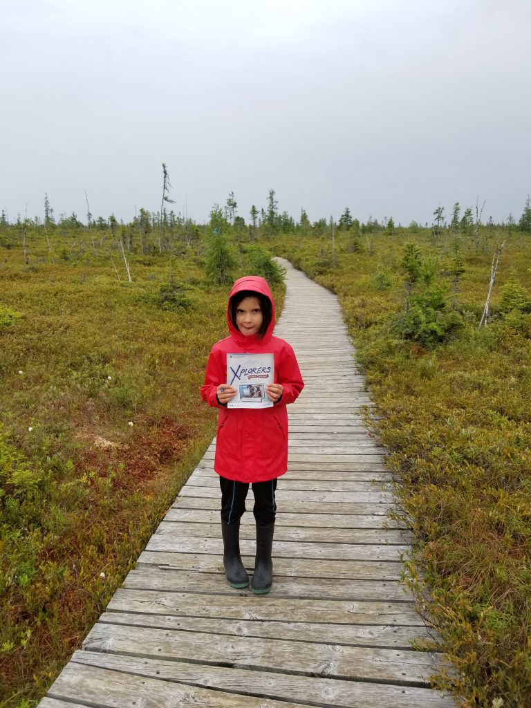 Girl showing an Xplorers booklet at the bog in Kouchibouguac National Park, in New Brunswick. She's wearing a red rain jacket, black pants, and black rain boots.