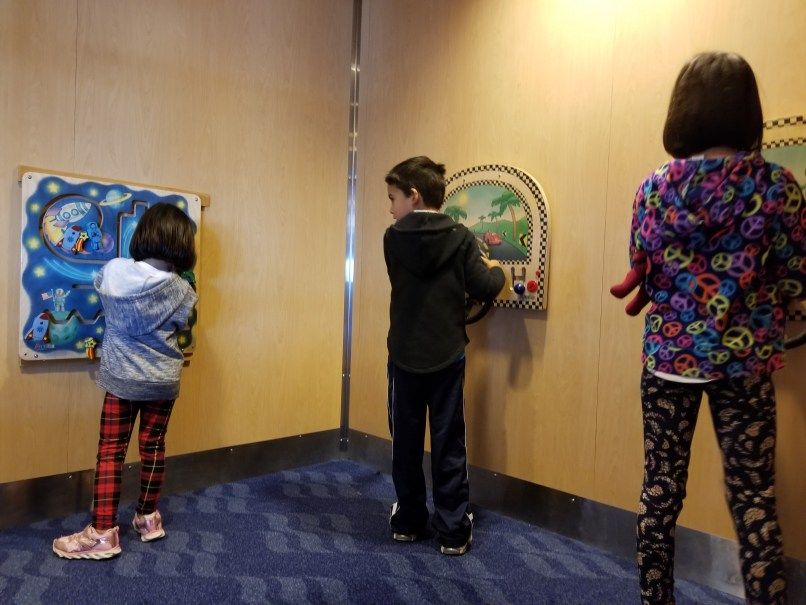 3 children playing with wall toys on the ferry to newfoundland