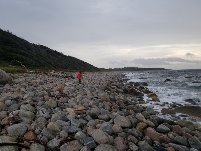 Girl in red rain jacket, black pants, and black rain boots, with a walking stick, walking along a rocky beach in Gros Morne National Park, Newfoundland