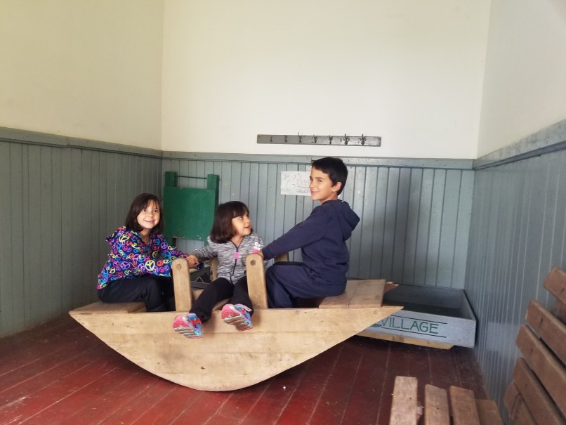 3 children playing at the one-room school house in Orwell Corner Historic Village, PEI