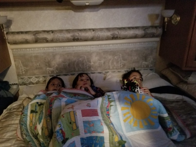 3 children, 2 girls and a boy, snuggling under a quilt.
