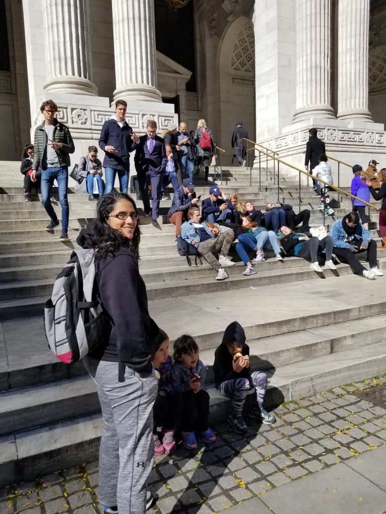 Mother and 3 children in front of the library steps outside the New York City Public Library. Several people are sitting on the steps. The mother is standing up and wearing a backpack.