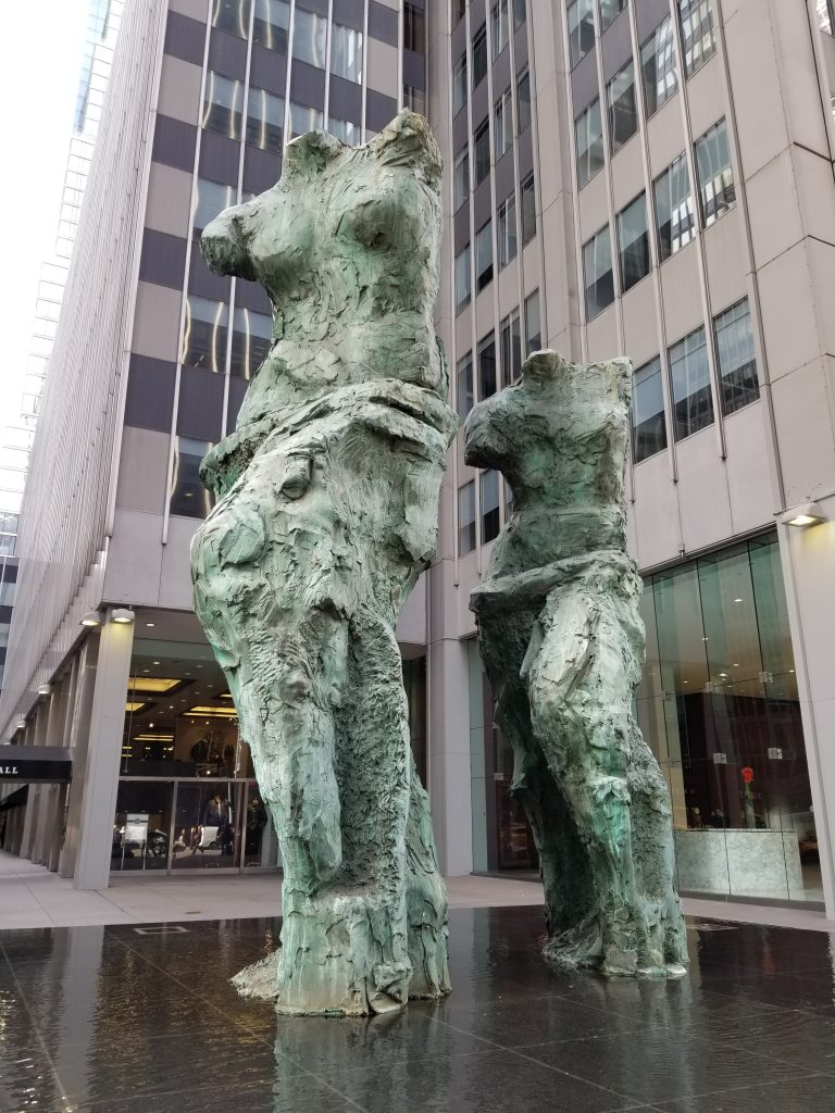 2 Female body sculptures with no heads in front of a building in NYC