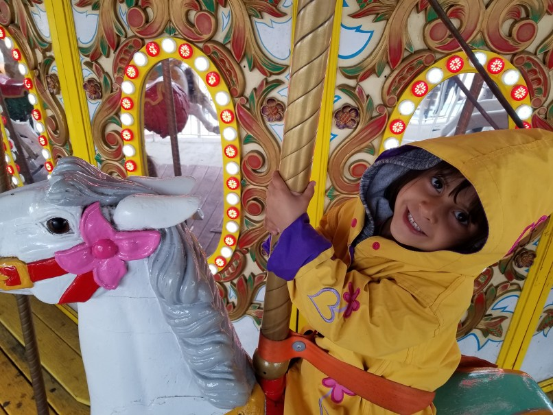 4-year-old girl wearing a yellow rain jacket, on a carousel horse at Six Flags Great Adventure