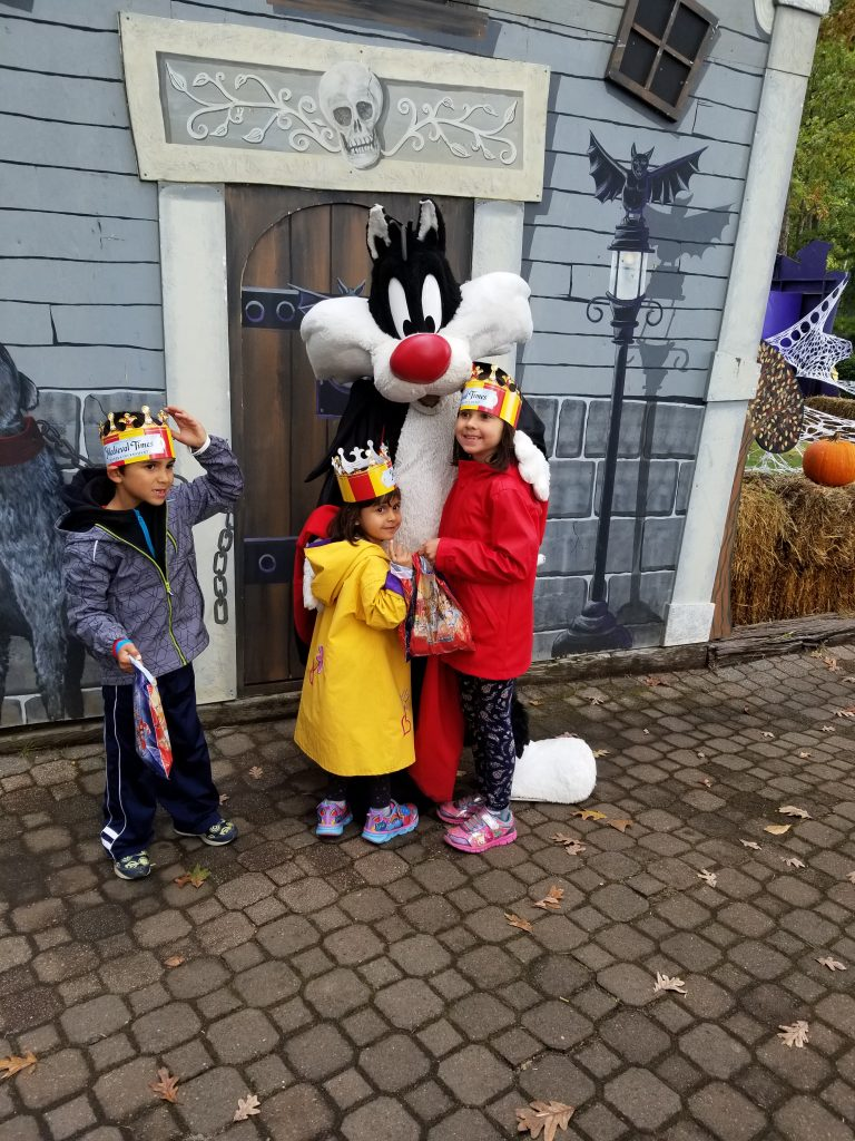 A boy and two girls pose for a photo with Sylvester the Cat at Six Flags Great Adventure in New Jersey