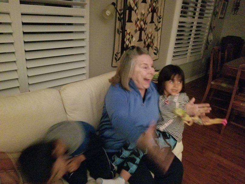 grandmother extending arms for a hug; one granddaughter on one side and a grandson on the other.