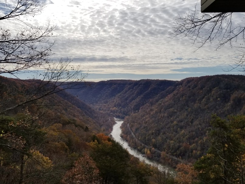 New River Gorge National River. A river can be seen flanked by two tree-covered mountains, and a white cloud-covered sky is above them.