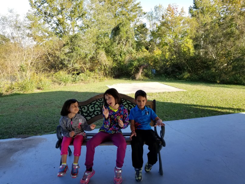 2 young girls and a young boy sitting on a bench outside at Charleston Tea Plantation