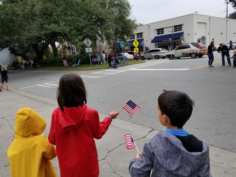 Three children waving small American flags at the Savannah Veteran's Day Parade