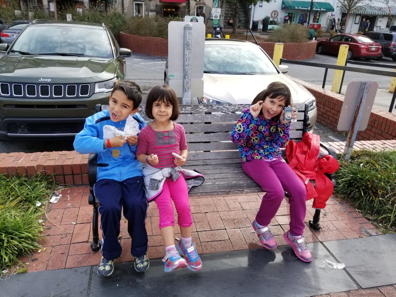 A by and two girls are sitting on a bench, eating treats they purchased from Savannah's Candy Kitchen.