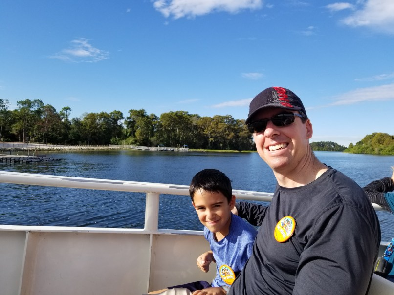 Father and son on a ferry. The lake can be seen behind them, with some trees on the other side of the water.
