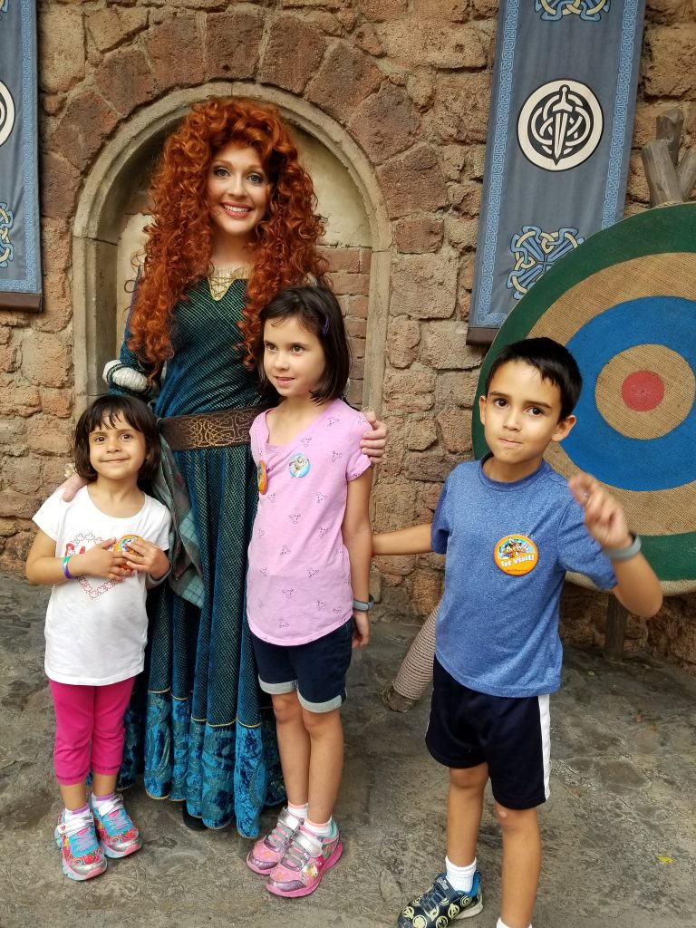 "Actress portraying the Disney character Merida, from the movie ""Brave,"" poses with two young girls and a young boy at Magic Kingdom in Disney World"