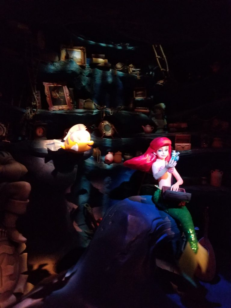 The Little Mermaid looks at one of her treasures as Flounder looks on. Mechatornic display at Little Mermaid Undersea Adventure, Magic Kingdom, Disney World
