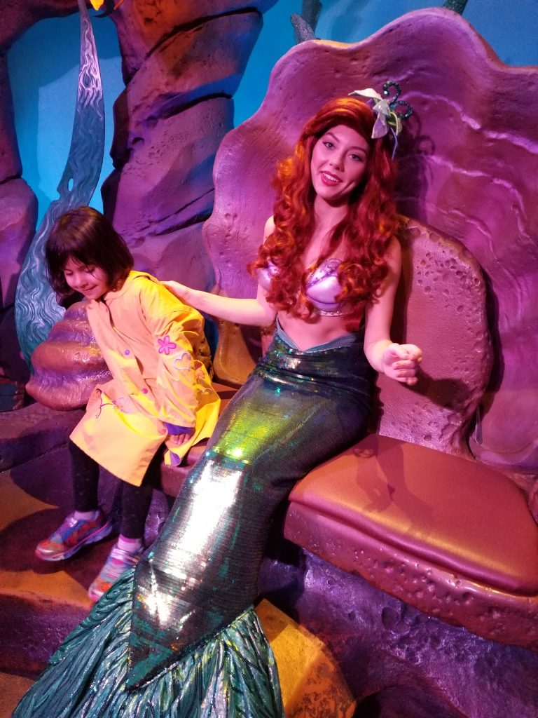 Girl sits with an actress portraying Ariel, from Disney's The Little Mermaid, at Magic Kingdom, Disney World