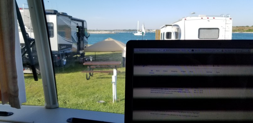 Laptop screen in foreground, ocean, sailboat, and RVs in background