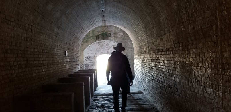 Man walking in Fort Pickens, towards an illuminated archway