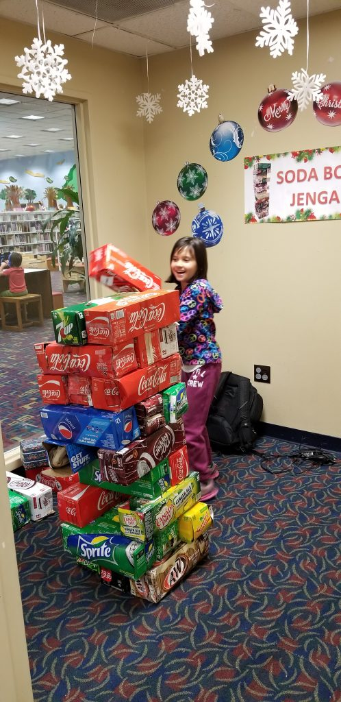 "A girl plays ""soda box jenga"" at Sterling Public Library in Baytown, Texas"