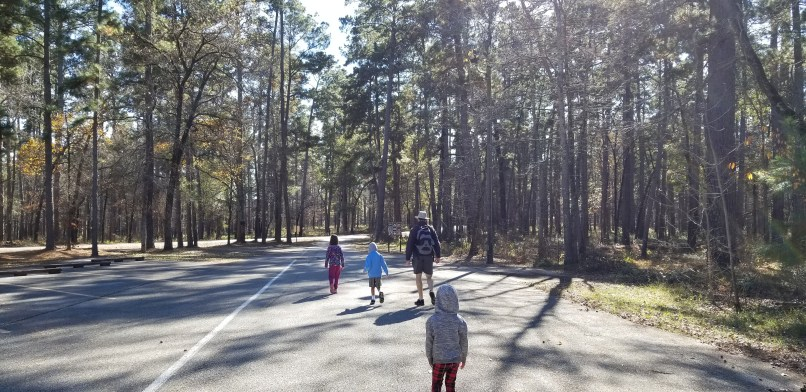 A father and three children walking into Sam Houston National Forest