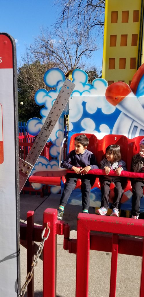A boy and a girl sitting in an amusement park ride at Six Flags Over Texas