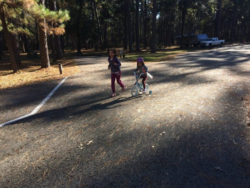 A 4-year-old girl rides a bike with training wheels, while her 8-year-old sister runs by her side at Sam Houston National Forest.