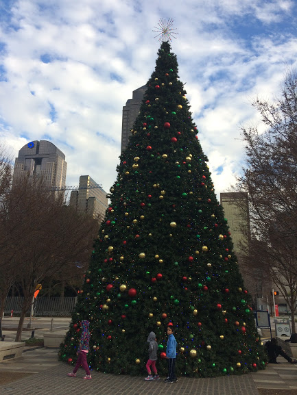 Giant Christmas tree in Klyde Warren Park, Dallas, Texas. Three children are looking at it.