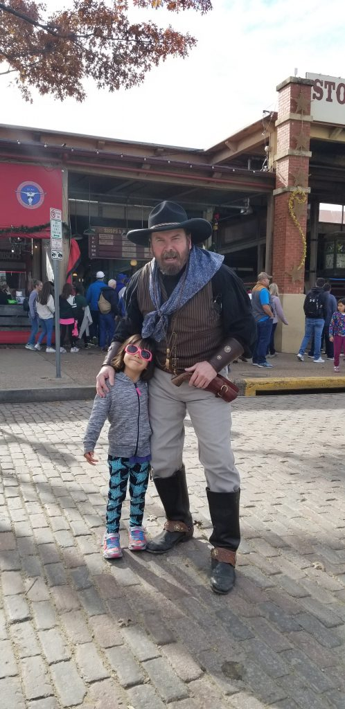 4-year-old girl poses with a man in period cowboy dress in fort wroth, texas