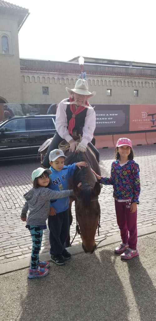 Cowboy with very long mustache on a horse. Three children are petting the horse. Fort Worth, Texas